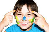 Happy kid with paints on hands and face — Stock Photo