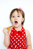 Little girl paints her lips with lipstick — Stock Photo