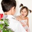 Stock Photo: The boy gives to the girl a rose on a white background