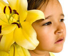Little girl with a yellow lily in her hair — Stock Photo