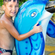 A little boy near the pool with a dolphin - Stock Photo