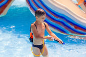 A little boy playing in the pool with a water pistol — Stock Photo