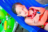 Little girl lies on a lounger by the pool — Stock Photo