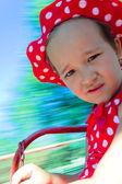Dziewczynka na karuzeli z tło zamazane pole — Zdjęcie stockowe