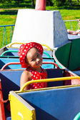 A little girl riding on a children's train — Stock Photo
