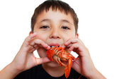 A little boy playfully eating crayfish — Stock Photo