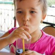 A little girl drinking juice at the cafe — Stock Photo
