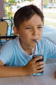 A little boy drinking juice at the cafe — Stock Photo