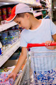Little boy in the shop chooses milk — Stock Photo