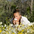 Woman suffering hay fever in field of  wildflower — Stock Photo