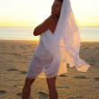 Sexy woman white cloth at sunset beach dancing — Stock Photo
