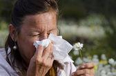 ワイルドフラワー フィールドで花粉症に苦しんでいる女性 — ストック写真