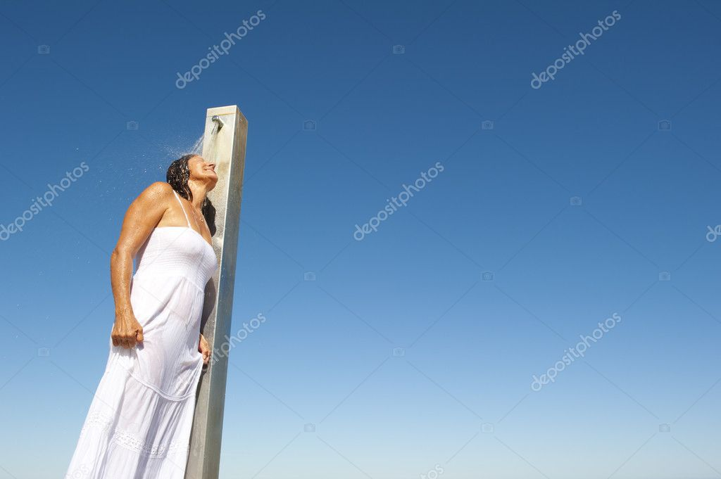 A pretty sexy looking woman having a shower outdoor, wearing a white wet soaked summer dress, isolated with blue sky as background and copy space. — Stock Photo #11112482