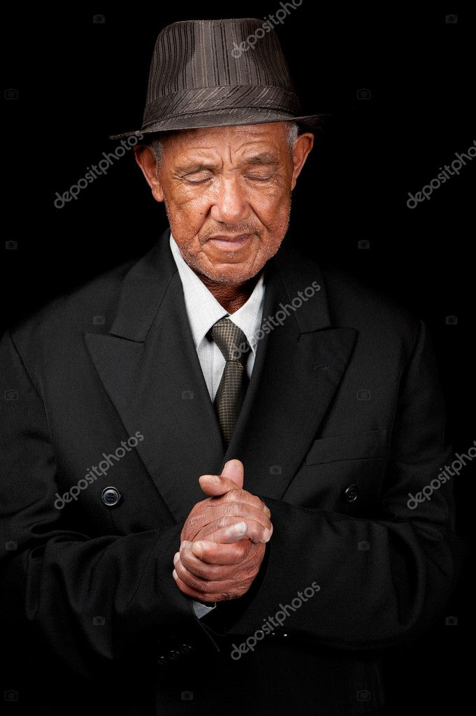 A senior man folds his hands whilst praying.  Stock Photo #11596740