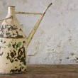 Antique watering can on a wooden table - Stockfoto