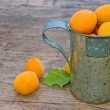 Apricots in a cup on a wooden background - Stockfoto