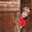 Cute girl peeping behind an old wooden door — Stock Photo #11576987