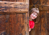 Cute girl peeping behind an old wooden door — Stock Photo