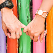 Hand in hand with colorful bamboo background — Stock Photo #11793657