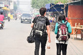 Young couple backpack on asphalt road — Zdjęcie stockowe