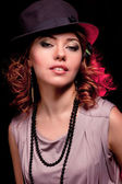 The beautiful woman in elegant to a hat on a black background cl — Stock Photo