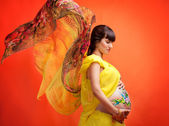 The pregnant girl with the drawn picture on a stomach in a yello — Stok fotoğraf
