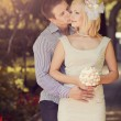 Wedding kissing pair in park - Stockfoto