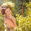 A beautiful girl in a light dress with flowers  in the park — Stock fotografie
