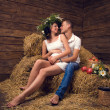 A couple in love during pregnancy in the hayloft — Stock Photo