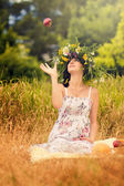 Pregnant woman in the dry grass tosses an apple — Stock Photo