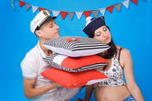 Couple in love during pregnancy in a marine style, with cushions — Stock Photo