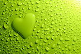 Water drops and heart shape on green background — Stok fotoğraf