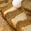 Bakery products and grain on wood - Stock Photo