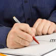 Hand writing by pen on checked notebook — Stock Photo
