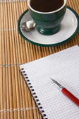 Cup of coffee and ink pen with checked notebook — Stock Photo
