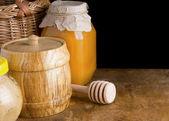 Jars and pot of honey on black background — Stock Photo