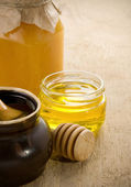 Honey in jars and pot on wood — Stock Photo