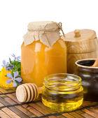 Honey, flowers and jars on white — Stock Photo