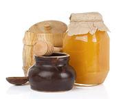 Jars and pot full of honey isolated on white — Stock Photo