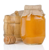 Glass and wooden jars full of honey isolated on white — Stock Photo