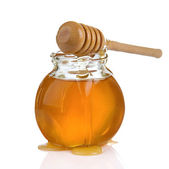 Glass jar of honey and stick isolated on white — Stock Photo