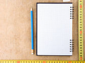 Notebook and tape measure on wood — Stock Photo
