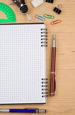 Acessórios de escola e notebook verificado na madeira — Foto Stock