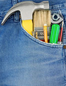 Tools in old blue jeans pocket — Stock Photo