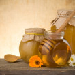 Jar of honey and flowers on wood — Stock Photo #10763150