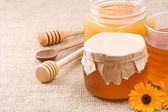Glass pot with honey on sack — Stock Photo