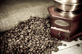 Coffee beans and grinder on sacking in night — Stock Photo