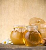 Glass jar of honey and stick — Stock Photo