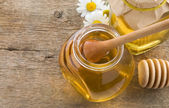 Glass jar of honey and stick on wood — Stock Photo