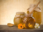 Jar of honey and flowers on wood — Stock Photo